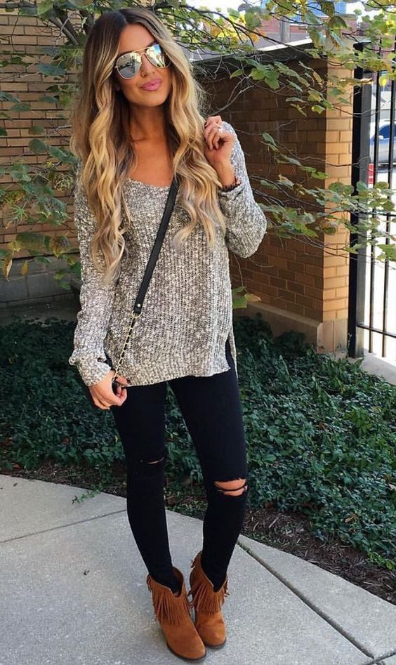 ripped black jeans, a neutral sweater and brown cowboy-styled boots