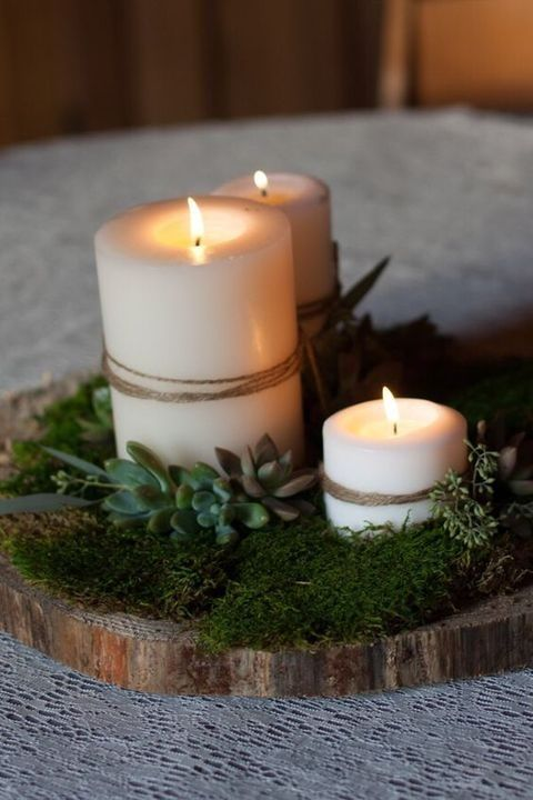 woodland-style centerpiece with moss, succulents and candles wrapped with twine