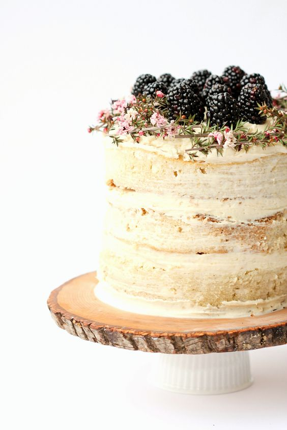 wood slice cake stand with a cup, a naked wedding cake with blackberries
