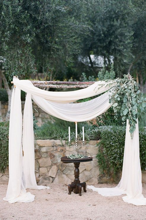 wedding arch with light fabrics and eucalyptus