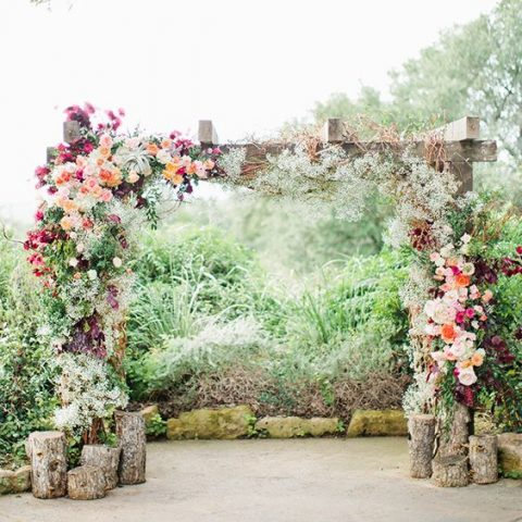 vibrant, lush floral arch with ranunculus, anemones, stock blooms and green jasmine vine