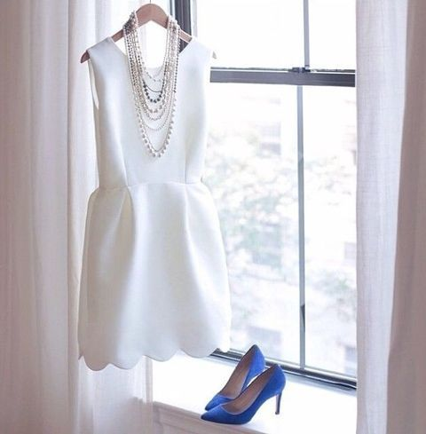 white plain mini dress with a scalloped hem and bold blue heels