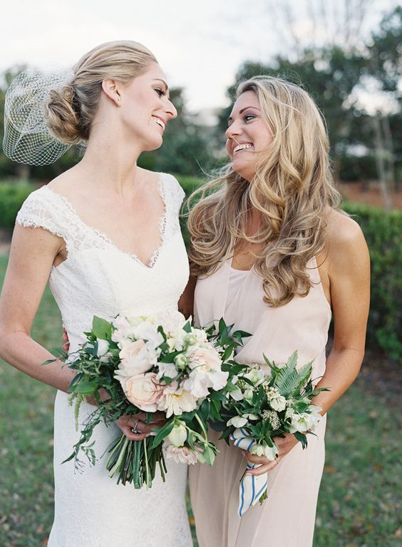 the bride in an ivory V-neck dress and her maid of honor in off-white