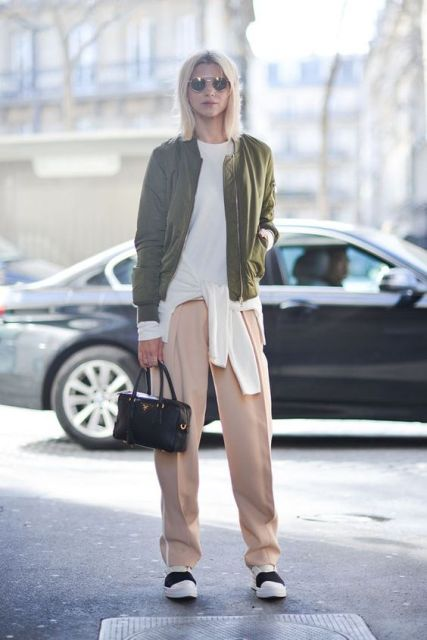 With olive green jacket, black and white shoes and small bag