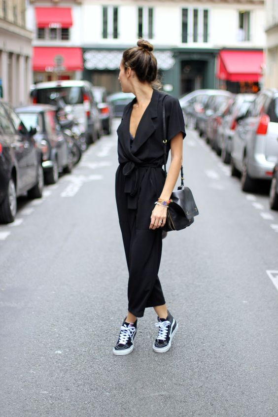 a black jumpsuit with a plunging neckline and black Vans
