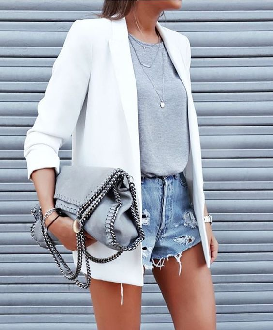 ripped blue denim shorts, a grey tee, a white jacket and layered necklaces