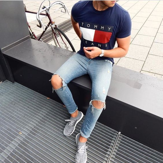 grey trainers, a printed navy t-shirt, ripped blue denim