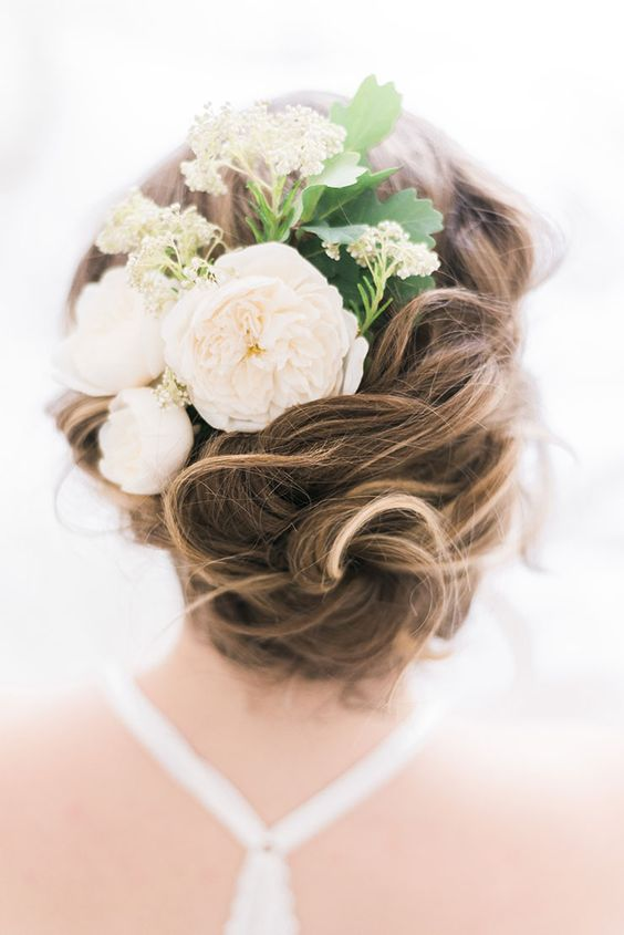twisted wedding updo with a fresh flower comb and leaves