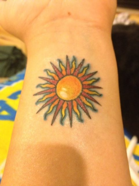 Yellow and red tattoo on the wrist