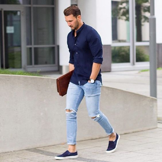 ripped blue jeans, a navy shirt and navy slip-ons
