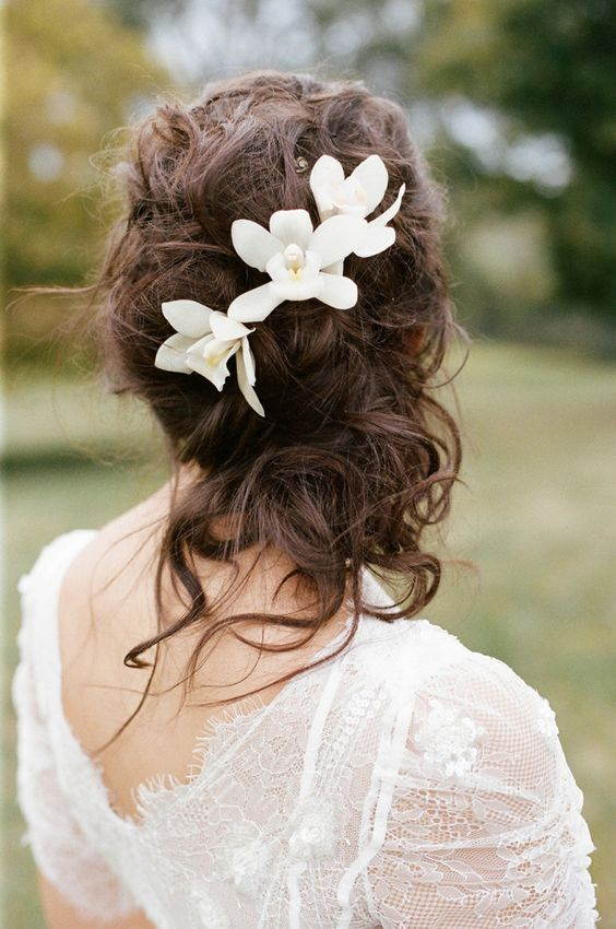 messy curly wedding half updo with tropical flowers
