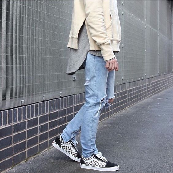 checked Vans, distressed denim, a grey t-shirt and a beige sweatshirt