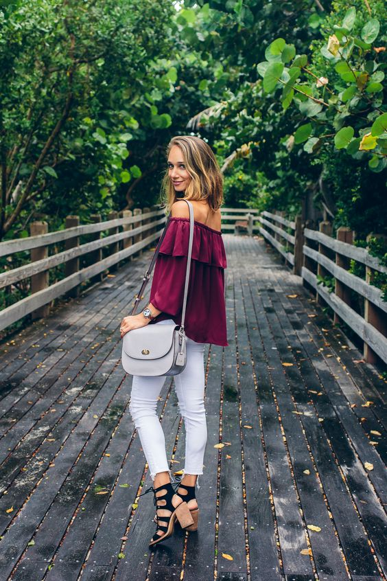 white jeans, a burgundy off the shoulder top, black lace up heels