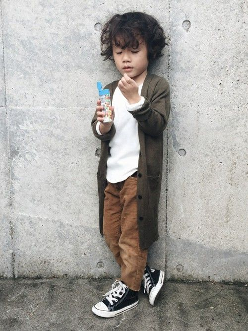 a white tee, brown pants, a brown grey cardigan and black sneakers