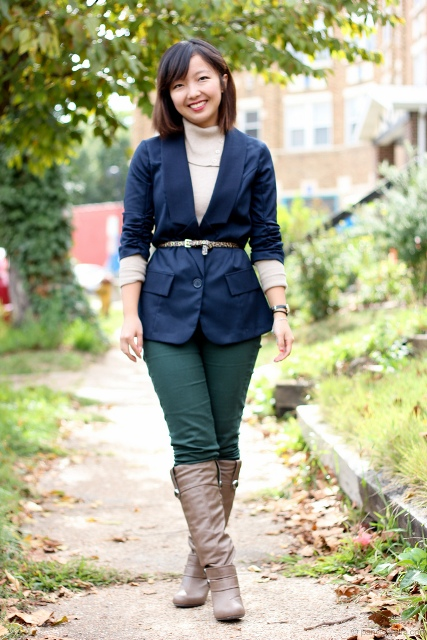 With navy blue jacket, belt and high boots