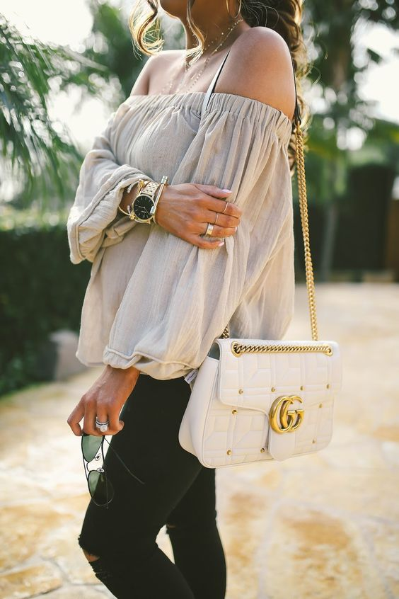 ripped black jeans, a neutral off the shoulder top