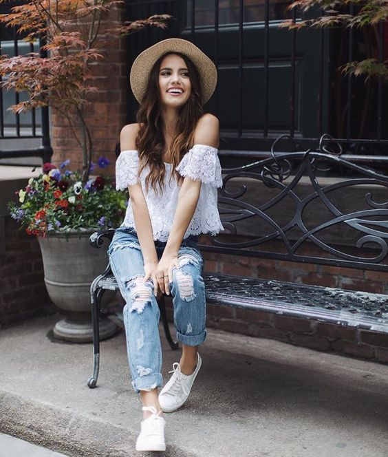 ripped blue jeans, a white lace off the shoulder top and white sneakers