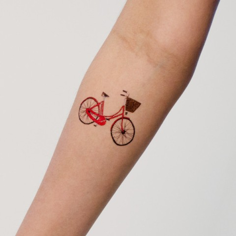 Red bicycle tattoo on the arm
