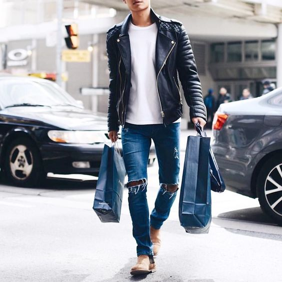 blue ripped jeans, a white tee, a black leather jacket and ocher boots