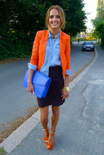 With denim shirt, mini skirt, orange heels and blue clutch