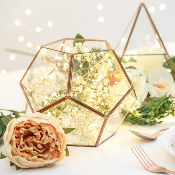 copper and glass pentagonal terrarium filled with lights is a cute idea