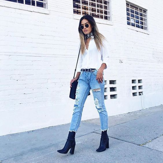 ripped distressed denim, a white shirt and navy boots