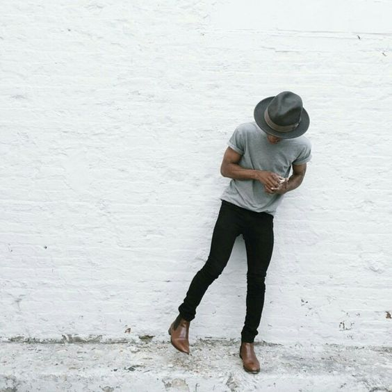black jeans, a grey tee, brown boots and a hat