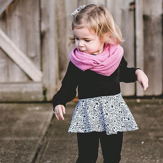 all-black look with a printed skirt and a pink scarf