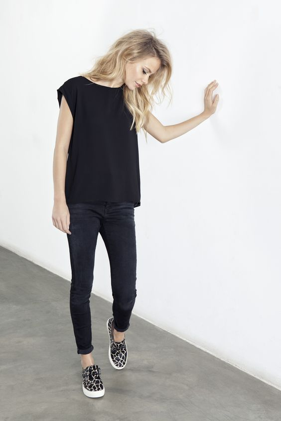 black jeans, a black sleeveless top and leopard slip-ons