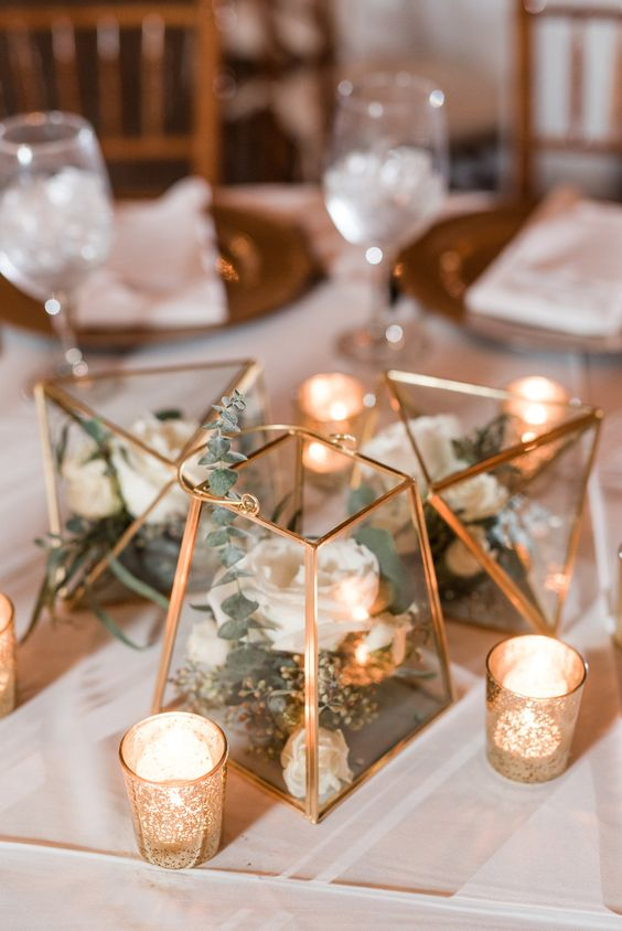 an organic wedding centerpiece with gold terrarium and gold mercury glass votives with romantic candles and white flowers with eucalyptus