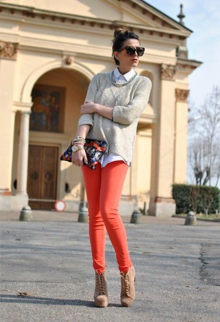 With white shirt, neutral sweater, boots and printed clutch