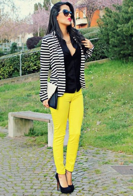 With black shirt, striped jacket, heels and black and white clutch