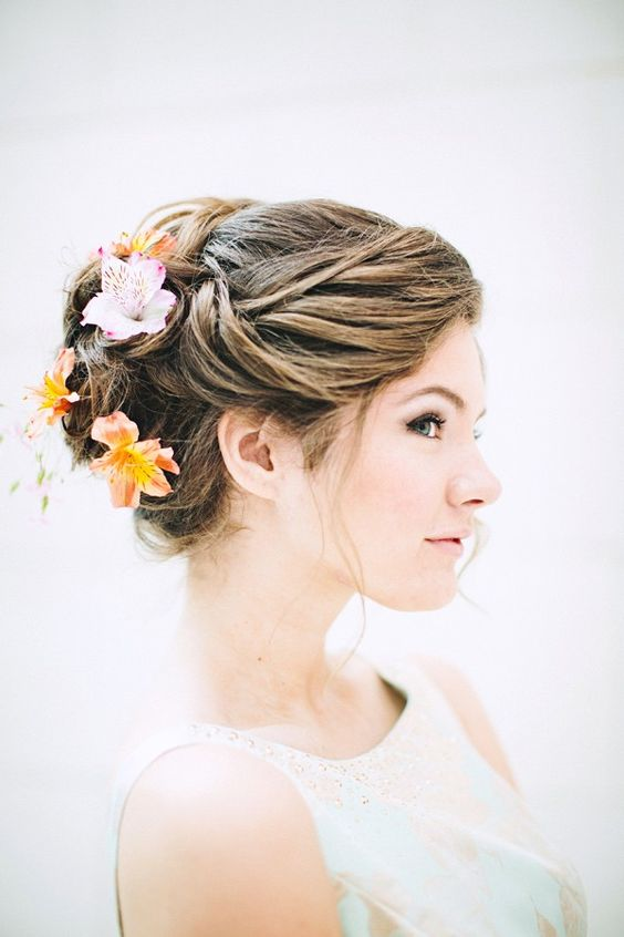 elegant wedding updo with tropical blooms in it