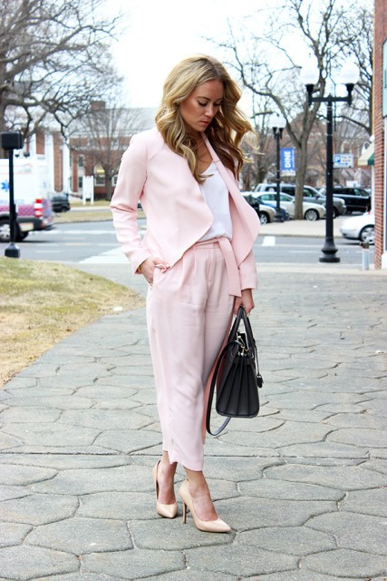 With white shirt, light pink jacket, pumps and black bag