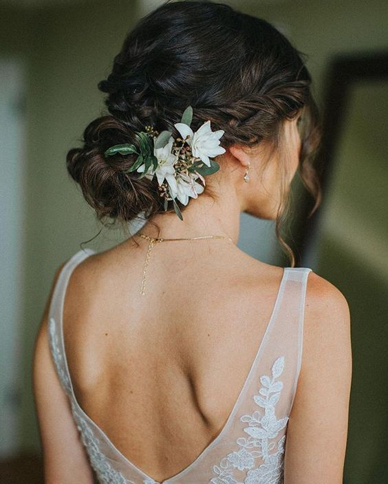 braided and twisted updo with hanging locks and flowers on one side