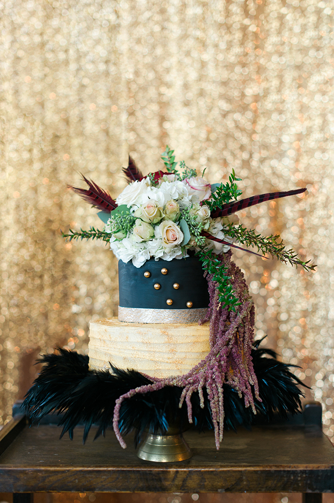 The wedding cake was done in black and half naked, with golden beads, topped with flowers and feathers