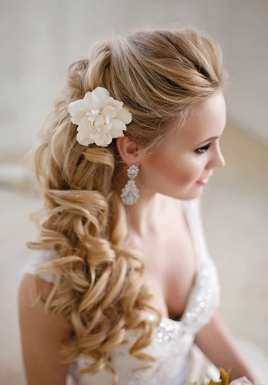 curly half updo on long hair and a single white bloom on the side