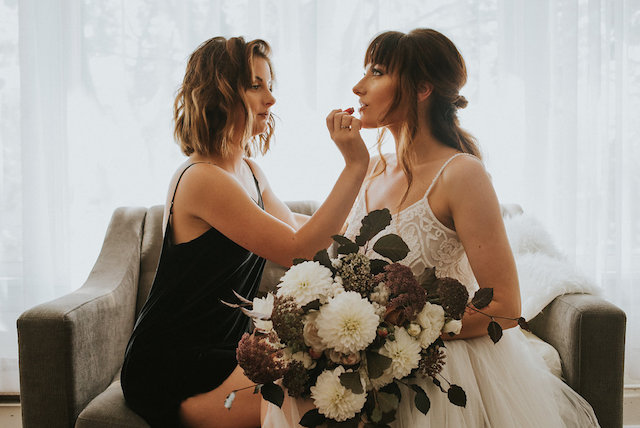 Bride having lipstick applied by bridesmaid | Lena Peterson Photography