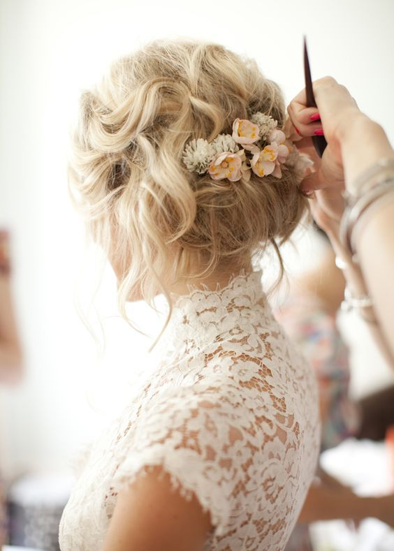 messy wedding updo with small neutral flowers
