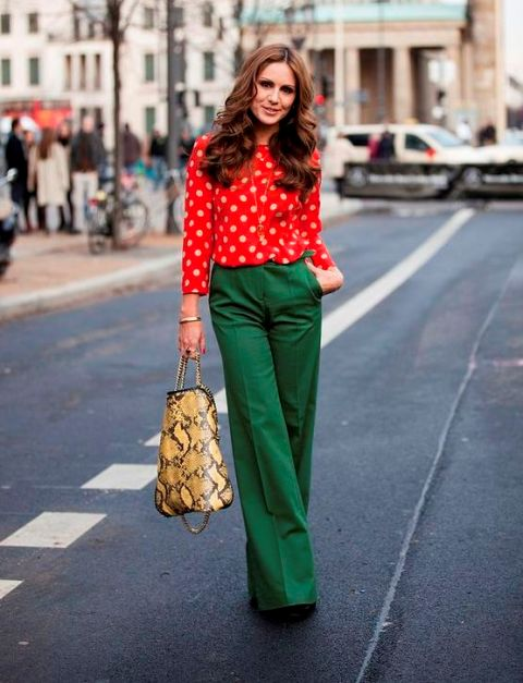 With red polka dot blouse, printed bag and black shoes