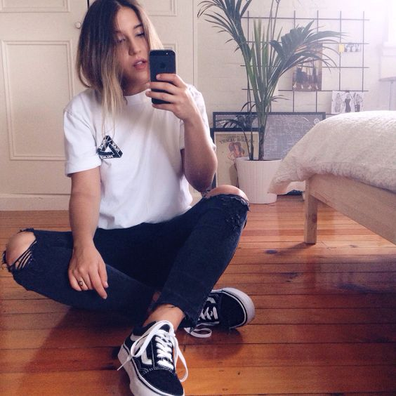 ripped jeans, a printed tee and black sneakers