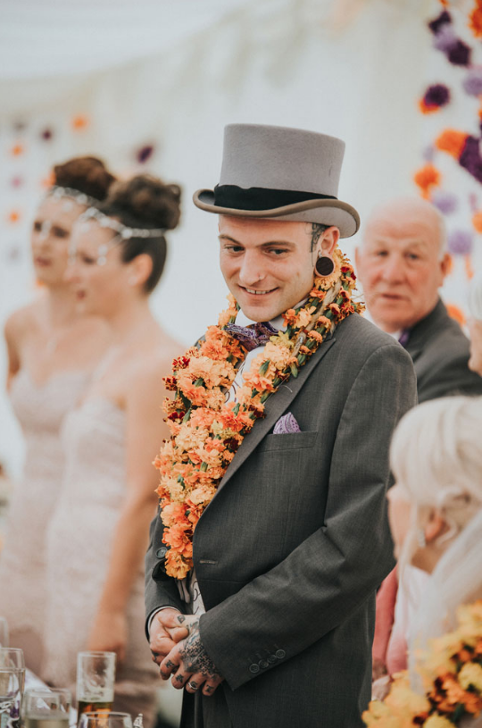 the groom wearing a flower necklace that everyone at the wedding was wearing