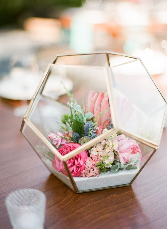 a terrarium filled with flowers and sand for a cool centerpiece