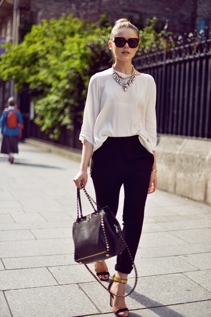 black cropped pants, a white blouse, a statement necklace and black sandals with gold details