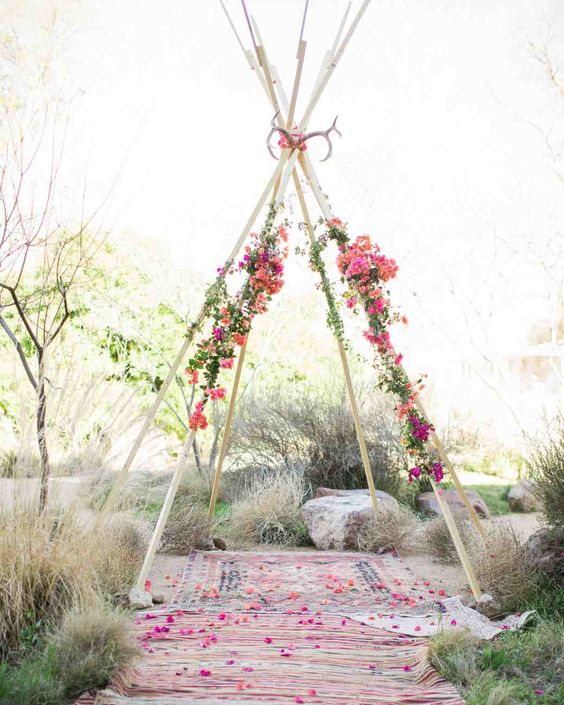teepee-style wedding chuppah with antlers and bold flowers