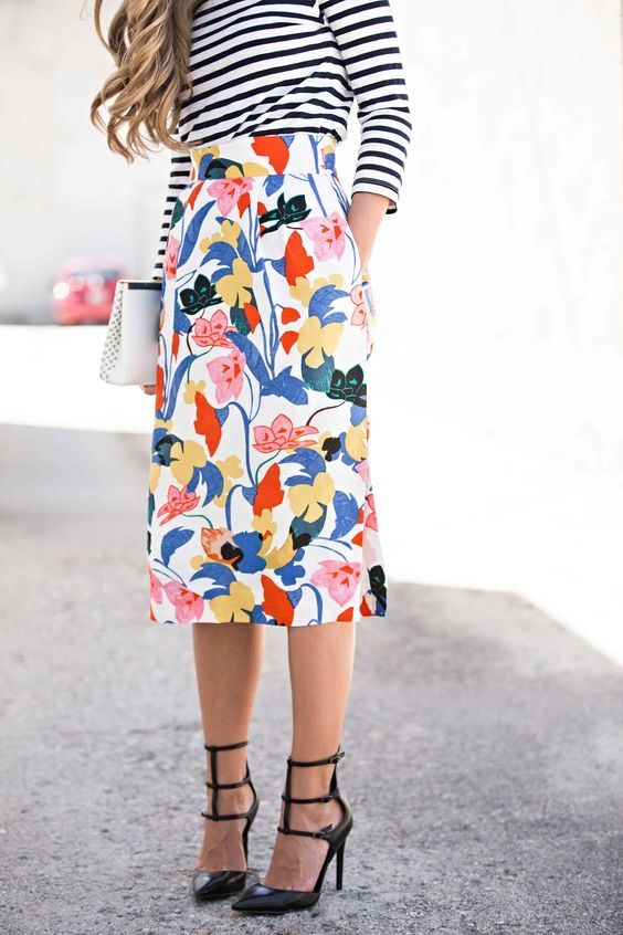 bold floral skirt, a striped long sleeve and black heels