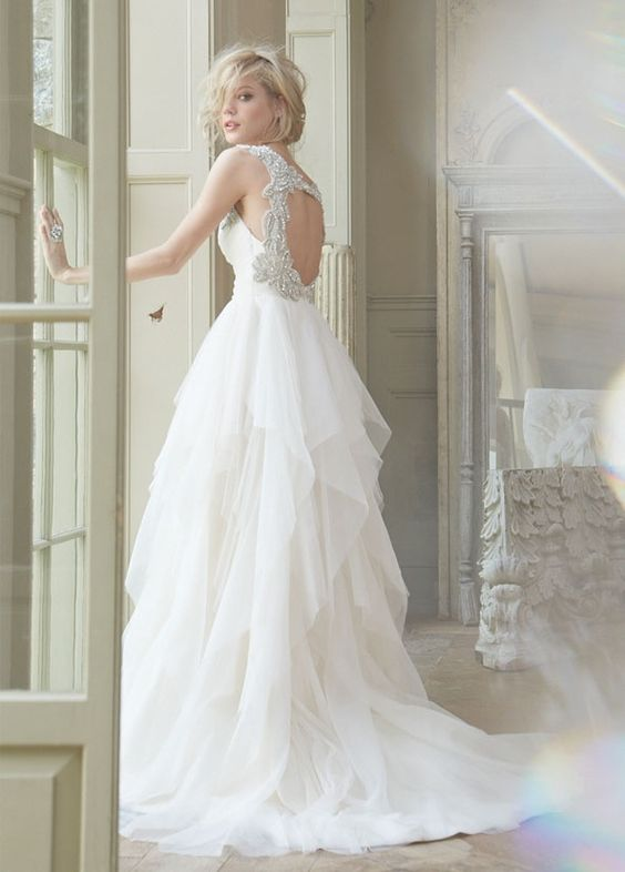 wedding dress with a heavily embellished circle cutout back and a draped tulel skirt