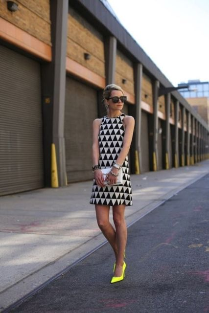 With geometric printed dress and white clutch