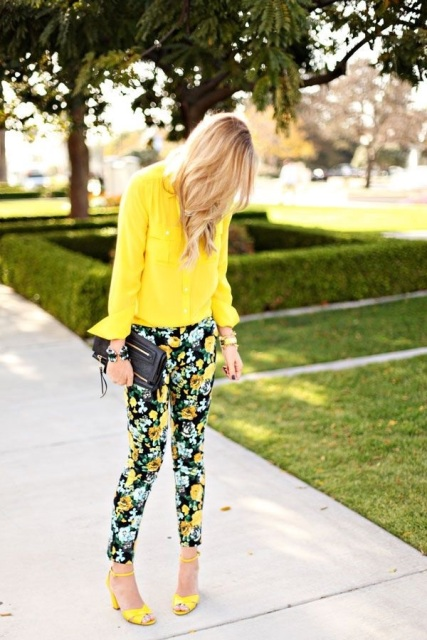 With yellow blouse, floral pants and black clutch