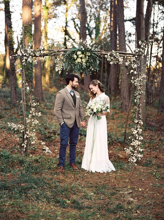 boho rough wood wedding arch with greenery and leaves for a fall wedding